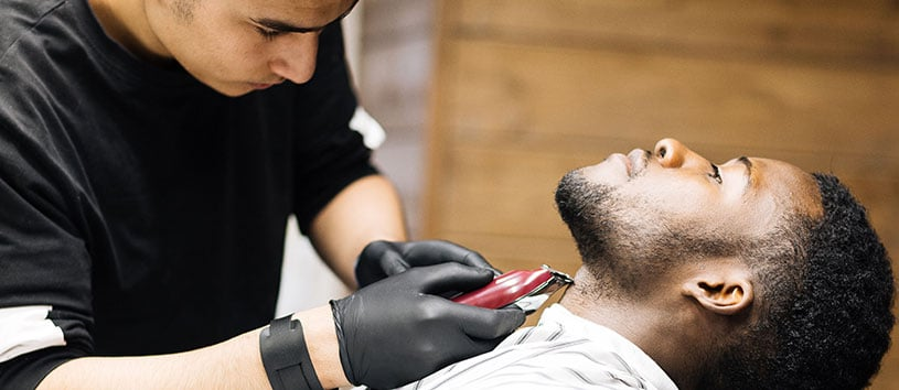 Male barber finishes trimming client's beard with electric clipper.