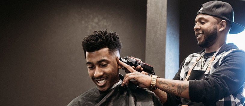 Barber client smiling while male barber finishes outlining the back of his head.