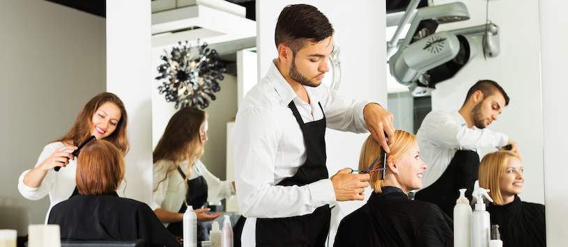 Male and female hairdressers working in a salon. For a great Cosmetology program check out Moler.