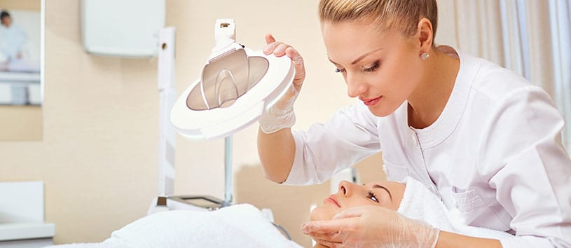 Esthetician examining a client's skin with a light.
